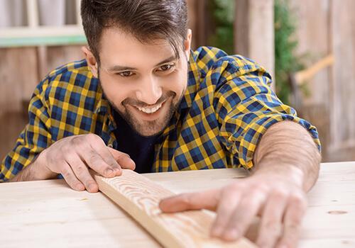 Closeup Foto eines jungen Tischlers bei der Arbeit
